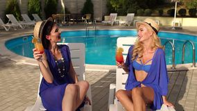 Two women drinking cocktail by pool and laugh. Two beautiful sexy woman in bikini and silk dresses sitting on the sun loungers by the pool with a cocktail and stock video