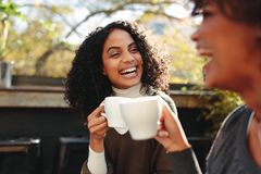 Two women drinking coffee at a coffee shop stock photo