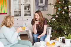 Two women drinking tea near a Christmas tree. Mother with daughter. Royalty Free Stock Photos