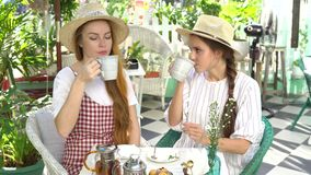 Two women drinking tea and talking, having good time. Two women in hats drinking tea and talking, having good time stock video
