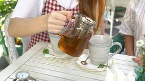 Two women drinking tea. Woman pouring tea from teapot into cup. stock video