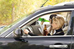 Two women driving a car while drinking Royalty Free Stock Photos