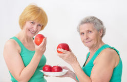 Two women eating an apples. Two senior women eating an apples Royalty Free Stock Photo