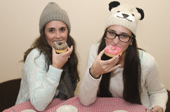 Two women eating donuts Stock Image