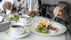 Two women eating fruits. Two women are eating fruits in restaurant Stock Photo