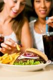 Two women eating hamburger and drinking soda