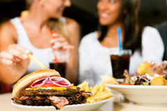 Two women eating hamburger and drinking soda. Two women - one is African American - eating hamburger and drinking soda in a fast food diner; focus on the meal Royalty Free Stock Photo