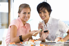 Two women eating in sushi bar, smiling, portrait Royalty Free Stock Photography