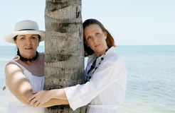 Two women embracing tree. Two women embracing a tree trunk, ocean in the background Stock Photography