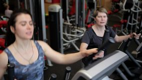 Two women are engaged on exercise machines in the gym. Trenerovka of women. Girls do exercises at a window. Sports. Gym stock video