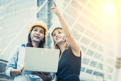 Two women engineering surveying for startup and launching new project. Building and construction concept. Business and happiness royalty free stock photo