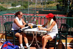Two women enjoying a cold drink after a game of tennis in the sun Stock Photos