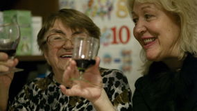 Two women enjoying a drink together stock footage