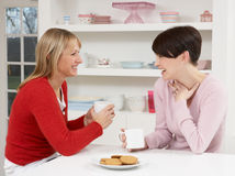 Two Women Enjoying Hot Drink In Kitchen. Smiling Stock Photography