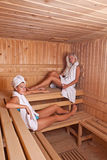 Two women enjoying a hot sauna Stock Photography