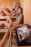 Two women enjoying a hot sauna Royalty Free Stock Images