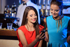 Two women enjoying with a smartphone Stock Image