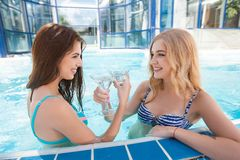 Two  women enjoying  summer vacation with cocktails by pool Royalty Free Stock Photo