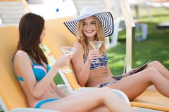 Two  women enjoying  summer vacation with cocktails by pool Stock Photos
