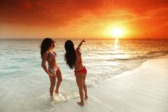 Two women enjoying sunset on beach Stock Photo