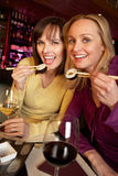 Two Women Enjoying Sushi In Restaurant Royalty Free Stock Photos