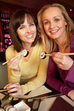 Two Women Enjoying Sushi In Restaurant Royalty Free Stock Photography