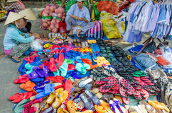 Two women examine the colorful sandals and shoes for sale at an outdoor market in Chan May, Vietnam Stock Photography