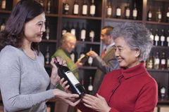 Two Women Examining Wine at a Wine Store Royalty Free Stock Photo