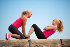 Woman doing situps outdoor. Two women exercise on beach doing squats stock images