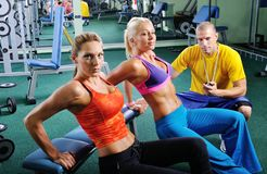 Two women exercise with personal fitness trainer Stock Images