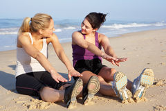 Two Women Exercising On Beach. Sitting On Sand Stretching Stock Photo
