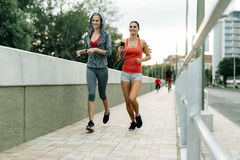 Two women exercising by jogging Royalty Free Stock Photos