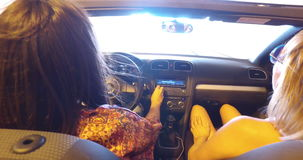 Two women exiting motorway tunnel in convertible car. Two young women exiting motorway tunnel in convertible car stock footage