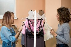 Two women, the fashion designer and the customer are considering underwear on a hanger. They discuss things and smile stock photography