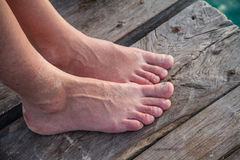 Two women feet together on a pier deck Stock Photography