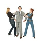 Two women fighting. Two women pulling a man in opposite sides Royalty Free Stock Photo