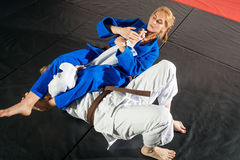 Two women are fighting on tatami. Judo, Jiu Jitsu. Two women are fighting on tatami. Blue and white kimano. Painful reception. Ground floor royalty free stock photography