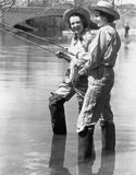 Two women fishing. (All persons depicted are no longer living and no estate exists. Supplier grants that there will be no model release issues Royalty Free Stock Image