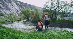 Two women with a fit bodies have a workout exercises at nature together they motivate each other while take some fresh