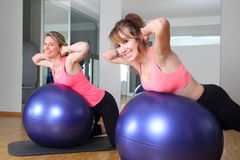 Two women in a fitness center on a Fitness Ball Royalty Free Stock Image