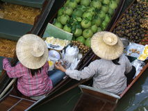 Two women in a floating market. Floating market in Thailand - Damnoen Saduak Floating Market, near Bangkok royalty free stock photography
