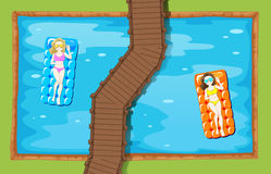 Two women on floating mat in the pool Royalty Free Stock Image