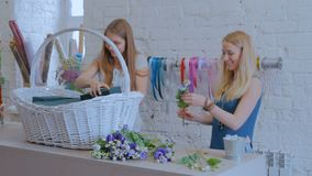 Two women florists making large floral basket with flowers at flower shop. Two professional women floral artists, florists making large floral basket with stock video footage