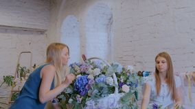 Two women florists making large floral basket with flowers at flower shop. Two professional women floral artists, florists making large floral basket with stock footage