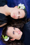 Two women with flowers in hair lie on a blue background Royalty Free Stock Photos