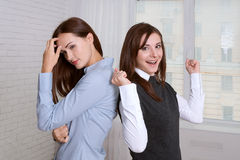 Two women in formal clothes standing back to back against the wi Royalty Free Stock Image