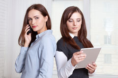 Two women in formal clothes standing back to back with gadgets Royalty Free Stock Photos