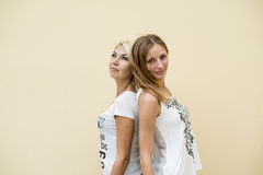 Two women friends, the beautiful brunette and blonde standing back to back, relax enjoy Stock Images