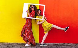 Girls posing with empty picture frame. Two women friends with blank photo frame standing against colored wall outdoors. Female travelers posing at camera with royalty free stock image