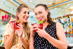 Two women friends in cafe bar drinking long drink Royalty Free Stock Images